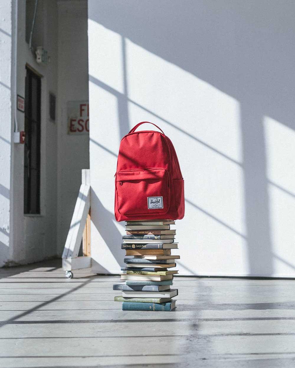 Un sac à dos Miller rouge sur une pile de livres dans un studio