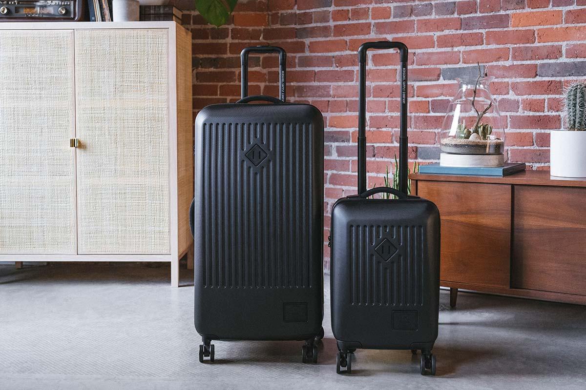 Un Trade Luggage Large et un Trade Luggage Carry-On noirs à côté l'un de l'autre dans un appartement en briques apparentes