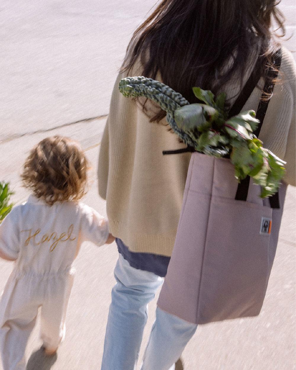 une femme avec un sac cabas rempli de légumes marche avec sa petite fille.