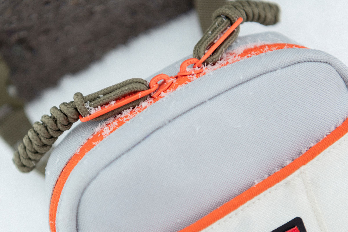 top of the crossbody showing the bright orange zip and braided cord zipper pulls