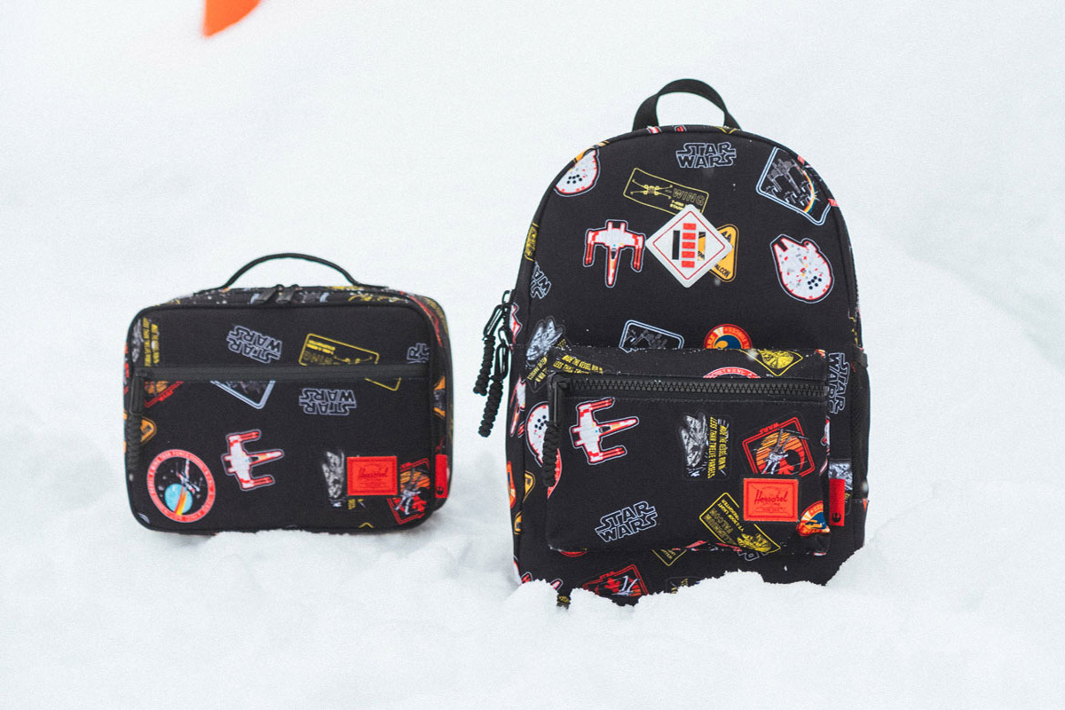 a pop quiz lunch box and a heritage backpack sit on a snowy background