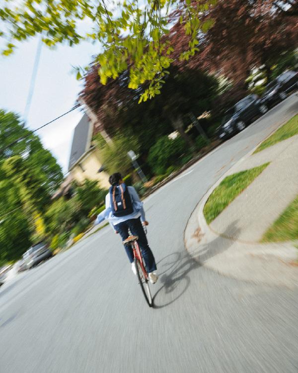 Un homme à vélo dans la rue porte un Herschel Little America Backpack en Black/Tan Synthetic Leather.