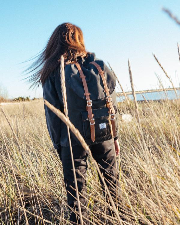 Une femme dans un champ de blé porte un Herschel Little America Backpack en Black/Tan Synthetic Leather